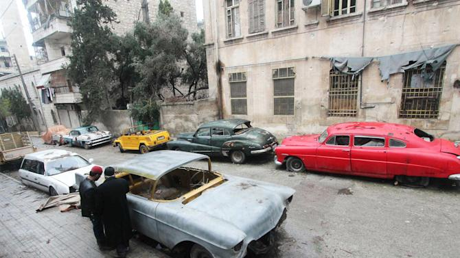 Mohamed Badr al-Din (R) stands next to his vintage cars along a street where he keeps them, in the al-Shaar neighborhood of Aleppo