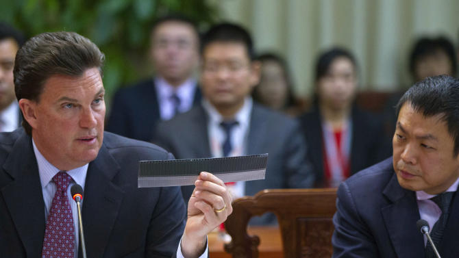 CEO of MiaSole John Carrignton, left, shows a piece of a thin-film solar panel, while Zhou Jiesan, right, an executive of Hanergy Group, watches during a press conference held at the headquarters of Hanergy Group in Beijing, China, Wednesday, Jan. 9, 2013. The Chinese company that bought Miasole, a California producer of thin-film solar panels, said it can make a success of the emerging technology where others have suffered huge losses. (AP Photo/Alexander F. Yuan)