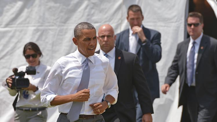 US President Barack Obama jogs to the stage to speak on the economy in Georgetown Waterfront Park on July 1, 2014 in Washington