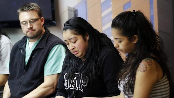 FILE - In this May 2, 2013, file photo, Johana Portillo, center, and her sister Ana Portillo hold hands while Dr. Shawn Smith looks on during a news conference at Intermountain Medical Center, in Murray, Utah. A Utah prosecutor said Monday, May 6, he plans to decide soon what charges to file against a teenager accused of punching Ricardo Portillo, a soccer referee who later died after slipping into a weeklong coma. (AP Photo/Rick Bowmer, File)