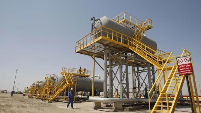 Iraqi workers walk through the Nassiriya oilfield in Nassiriya