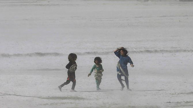 Afghan children walk during a dust storm in Kabul, Afghanistan