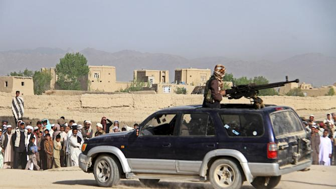 A member of the Taliban insurgent (top) and other people stand at the site of the execution of three men, accused of murdering a couple during a robbery, in Ghazni Province