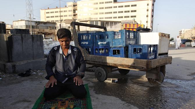 In this Sept. 8, 2012 photo, Shiite Hussein Abdul Ali, 16, prays next to his soft drink cart in the Shiite holy city of Najaf, Iraq, 100 miles (160 kilometers) south of Baghdad. He earns about U.S. $4 per day. Ten years after the U.S.-led invasion, the county is mired in widespread instability and political corruption. Nevertheless, interviews and discussions across the country with more than a dozen Iraqi teenagers and young adults reveal a resiliency and refusal to abandon hope. (AP Photo/Alaa al-Marjani)