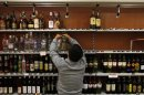 A shop owner removes bottles of hard liquor from a shelf in Prague