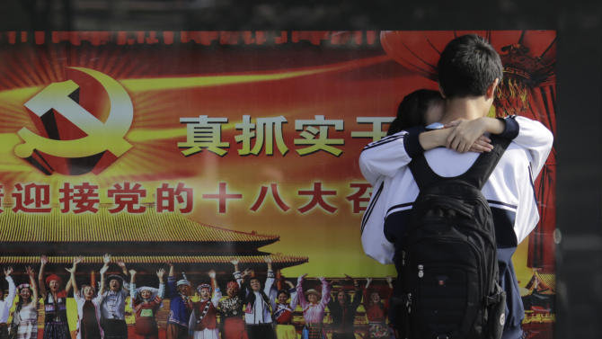 A young couple share a light moment Monday, Nov. 5, 2012, near the official propaganda poster in Shanghai, China, of the Chinese Communist Party's 18th National Congress which is scheduled to begin on Nov. 8 in Beijing. Chinese have long been fascinated with U.S. presidential elections, but interest is particularly high this year because Americans are voting at the same time Beijing is going through its own political transition. (AP Photo/Eugene Hoshiko)