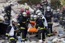 French firemen carry a victim in the rubble of a building after an explosion collapsed it, in Rosny-sous-Bois, outside Paris, Sunday, Aug. 31, 2014. French authorities say a four-story building in a northeastern Paris suburb has collapsed after an explosion, killing a child. More people are thought to underneath the rubble. Speaking on i-Tele, fire department spokesman Gabriel Plus said around 10 people were evacuated from the building in Rosny-sous-bois that occurred early Sunday morning. Plus said that around another 10 people could still be underneath the rubble, and emergency teams were working hard to rescue people who might be trapped.