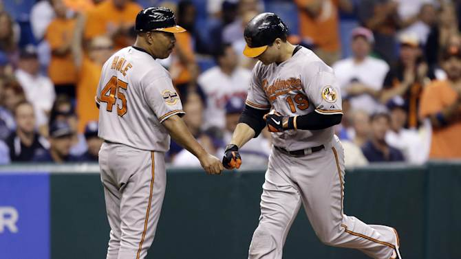 Baltimore Orioles' Chris Davis, right, bumps fists with third base coach DeMarlo Hale after Davis hit a fourth-inning home run off Tampa Bay Rays starting pitcher James Shields during a baseball game, Tuesday, Oct. 2, 2012, in St. Petersburg, Fla. (AP Photo/Chris O'Meara)