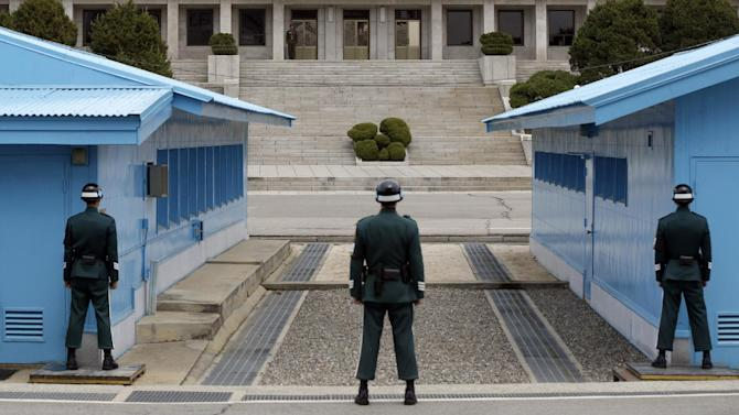 AP10ThingsToSee - A North Korean soldier, background, looks to the southern side as South Korean soldiers stand guard at the border village of Panmunjom, which has separated the two Koreas since the Korean War, in Paju, north of Seoul, South Korea on Wednesday, April 10, 2013. (AP Photo/Lee Jin-man, File)
