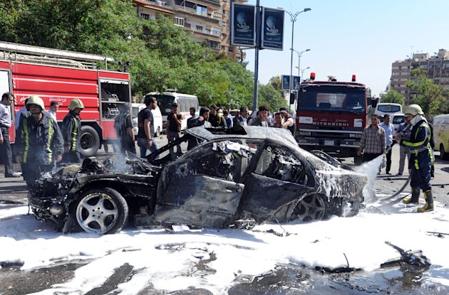 This photo released by the Syrian official news agency SANA, shows Syrian fire fighters extinguishing burning cars after a car bomb exploded in the capital's western neighborhood of Mazzeh, in Damascus, Syria, Monday, April. 29, 2013. State-run Syrian TV says the country's prime minister has escaped an assassination attempt when a bomb went off near his convoy. The TV says Prime Minister Wael al-Halqi was unhurt in the attack in the capital's western neighborhood of Mazzeh. (AP Photo/SANA)