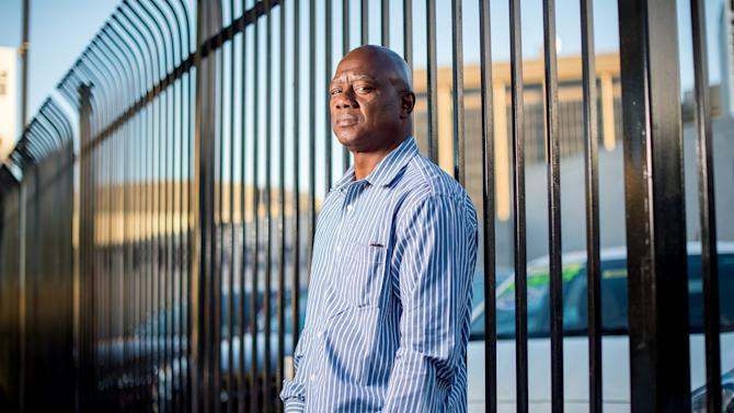 Arthur Scott, who was paroled in March 2014 after serving time on his 22nd auto theft conviction, stands in front of an Oakland, Calif., Acura dealership on Tuesday, June 24, 2014. Scott, determined to stay out of jail and currently working while taking vocational classes, says he had stolen more than five cars from the dealership. (AP Photo/Noah Berger)