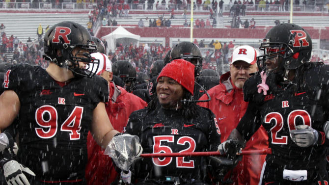 FILE - This Oct. 29, 2011 file photo shows paralyzed former Rutgers football player Eric LeGrand (52), center in wheelchair, coming onto the field with players Scott Vallone (94) and Khaseem Greene (20), before an NCAA college football game against West Virginia in Piscataway, N.J. LeGrand has been signed by the Tampa Bay Buccaneers. LeGrand broke two vertebrae and suffered a serious spinal cord injury on Oct. 16, 2010 during a kickoff return against Army. His coach at Rutgers then, Greg Schiano, now is coach of the Bucs. (AP Photo/Mel Evans, File)