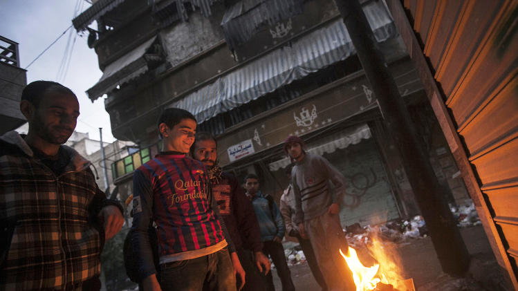Syrians light a fire to keep warm in Aleppo, Syria, Tuesday, Dec. 4, 2012. Temperatures dropped to 16 degrees Celsius (60.8 Fahrenheit) in Aleppo. (AP Photo/Narciso Contreras)