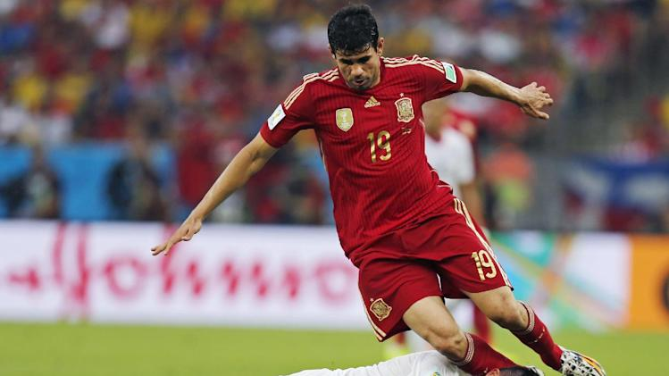 Spain's Diego Costa trips over Chile's Gary Medel during the group B World Cup soccer match between Spain and Chile at the Maracana Stadium in Rio de Janeiro, Brazil, Wednesday, June 18, 2014
