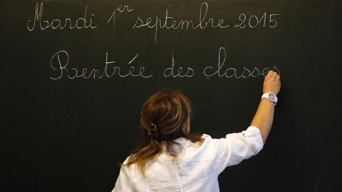A teacher writes on the blackboard prior to the arrival of French President Hollande at the Groupe Le Marais primary school on the first day of the new school year in Pouilly-sur-Serre