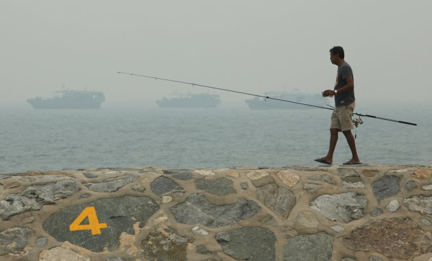 Man fishes on breakwater along East Coast park on a hazy day in Singapore