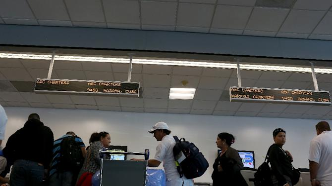 People wait in line to check luggage at the ABC Charters American Airlines flight to Havana, Cuba at Miami International Airport on December 19, 2014 in Miami, Florida