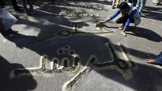 "A man writes a message using sand in the street near Tahrir Square in Cairo, Egypt, Monday, Dec. 10, 2012. The sign reads ""down with the supreme leader's rule."" (AP Photo/Petr David Josek)"