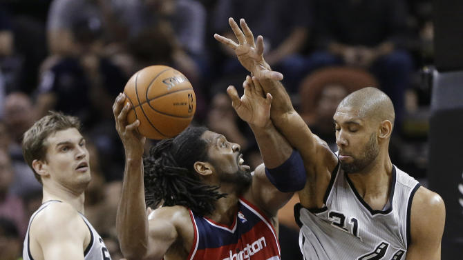 Washington Wizards' Nene (42) works against San Antonio Spurs' Tim Duncan (21) and Tiago Splitter, left, during the first half of an NBA basketball game, Saturday, Feb. 2, 2013, in San Antonio. (AP Photo/Eric Gay)