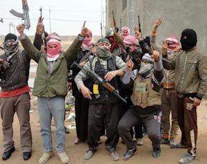 Iraqi men from local tribes brandish their weapons …
