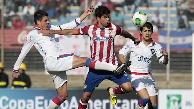 Guillermo de los Santos (L) of Uruguay's Nacional and Diego Costa (C) of Spain's Atletico Madrid fight for the ball during a friendly match in Montevideo, August 4, 2013 (Reuters)