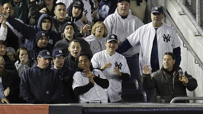 New York Yankees fans react as Baltimore Orioles left fielder Nate McLouth catches a ball hit by Yankees' Jayson Nix during the fifth inning of Game 4 of the American League division baseball series on Thursday, Oct. 11, 2012, in New York. Yankees' Russell Martin was out at first base for a double play.  (AP Photo/Kathy Willens)
