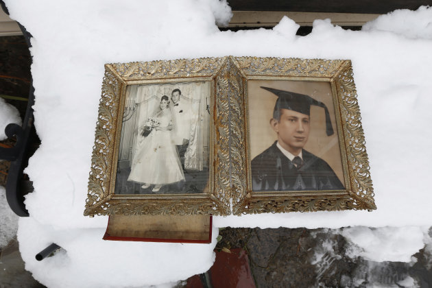 Photographs of Elliott Miller's wedding day and graduation lay on a snow covered bench as Jeanene Miller tries to dry out the pictures of her in-laws which were damaged during floods caused by Superst