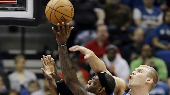 Miami Heat's LeBron James shoots as Minnesota Timberwolves' Greg Stiemsma, right, and Mikael Gelabale, left, of France, defend in the first half of an NBA basketball game, Monday, March 4, 2013, in Minneapolis. (AP Photo/Jim Mone)