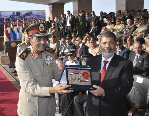 Egypt's new President Mursi poses with a gift from Field Marshal Tantawi, head of Egypt's ruling SCAF, during a ceremony where the military handed over power to Mursi at a military base in Hikstep, east of Cairo