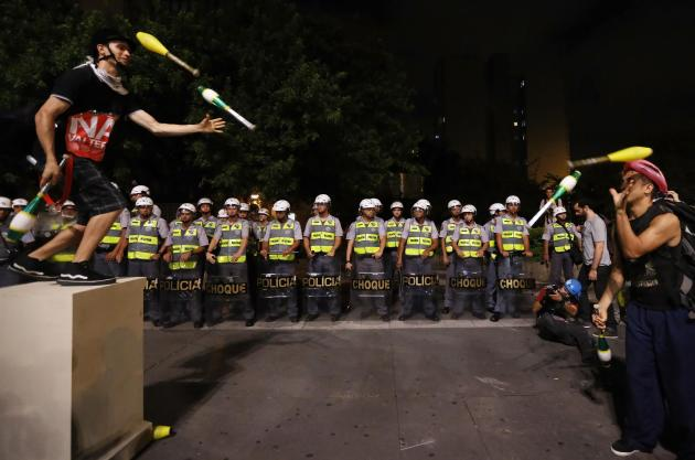 Demonstrators and jugglers perform in front of military policemen during a protest against the 2014 World Cup, in Sao Paulo