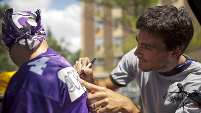 Minnesota Vikings kicker Chris Kluwe signs a jersey with his new number and his Twitter handle on the back for fan Todd Glocke, of St. Paul, Minn., Sunday, July 31, 2011, at the NFL football team's training camp in Mankato, Minn. Quarterback Donovan McNabb wanted Kluwe's number 5 jersey, so Kluwe opted to go with number 4, as long as no one else was using it. (AP Photo/Star Tribune, Jeff Wheeler) MINNEAPOLIS-AREA TV OUT  ST. PAUL OUT  MAGS OUT