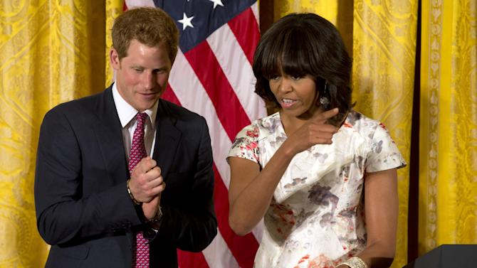 First lady Michelle Obama gestures during a surprise visit from Prince Harry at an event in honor of military mothers in the East Room of the White House in Washington, Thursday, May 9, 2013. (AP Photo/Jacquelyn Martin)