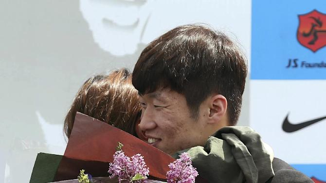 Park Ji-sung, right, a former Manchester United regular and one of the stars of South Korea's run to the 2002 World Cup semifinals, hugs a fan during a press conference in Suwon, South Korea, Wednesday, May 14, 2014. Park announced his retirement from top-flight football