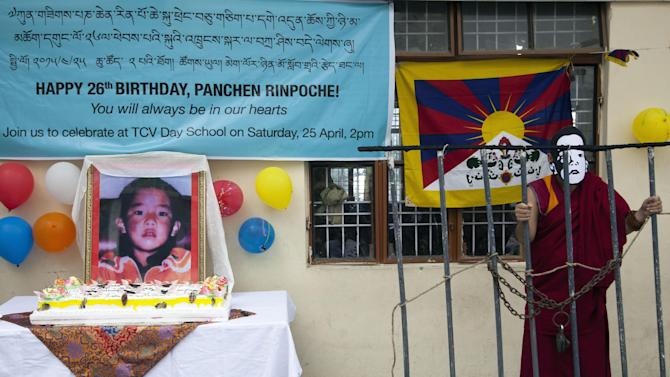 An exile Tibetan schoolboy wears a mask of Gedhun Choekyi Nyima, the Panchen Lama chosen by Dalai Lama, during an event to mark his 26th birthday in Dharmsala, India, Saturday, April 25, 2015. Panchen Lama, the second highest leader in Tibetan Buddhist hierarchy, who has not been seen since 1995. (AP Photo/Ashwini Bhatia)