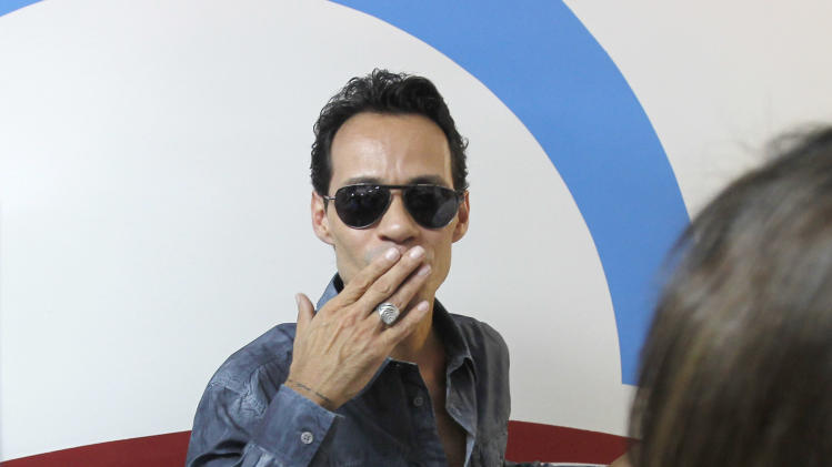 Latin music artist Marc Anthony,  whose family is from Puerto Rico, blows a kiss to supporters after the opening of a new Obama For America-Florida office in the Little Havana area of Miami, Thursday, Aug. 2, 2012. Puerto Ricans living in Florida's Interstate 4 corridor are drawing unprecedented attention from the presidential campaigns. (AP Photo/Alan Diaz)