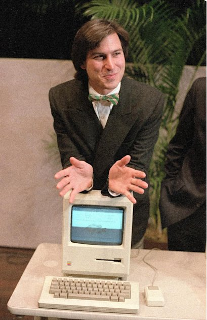 FILE - In this Jan. 24, 1984 file photo, Steve Jobs, chairman of the board of Apple Computer, leans on the new Macintosh personal computer following a shareholder's meeting in Cupertino, Ca.  Appl