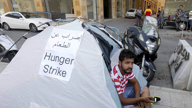 """Waref Sleiman, a """"You Stink"""" activist, rests in his tent during a hunger strike calling on minister Mohamad Al Machnouk to resign over a rubbish disposal crisis, in front of the environment ministry in downtown Beirut"""