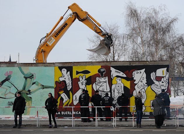 Police officers guard a construction site and sections of the East Side Gallery, while parts of the former Berlin Wall are removed in Berlin, Germany, Wednesday March 27, 2013. Work crews backed by ab