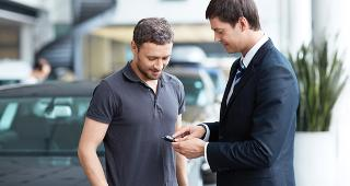 Young man with car salesman copyright LuckyImages/Shutterstock.com