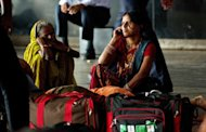 An Indian passenger talks on her mobile phone as she waits at a railway station following an overnight regionwide power outtage in New Delhi