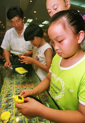 FILE - In this July 13, 1997 file photo, nine-year-old Zhu Ying tries out a Tamagotchi electronic pet at a Beijing department store. Bandai America Inc. and Sync Beatz Entertainment are hoping to revive the electronic pet craze of the 1990s with a new mobile app launching Thursday, Feb. 14, 2013, for Android devices. The app duplicates the egg-shaped plastic toy that became a must-own sensation after it was first released in 1996 in Japan. (AP Photo/Greg Baker, File)