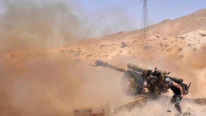 A Syrian soldier fires artillery shells towards Islamic State (IS) jihadists in northeastern Palmyra on May 17, 2015