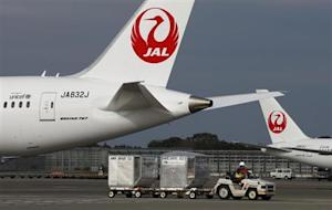 A airport worker drives a luggage transport vehicle…