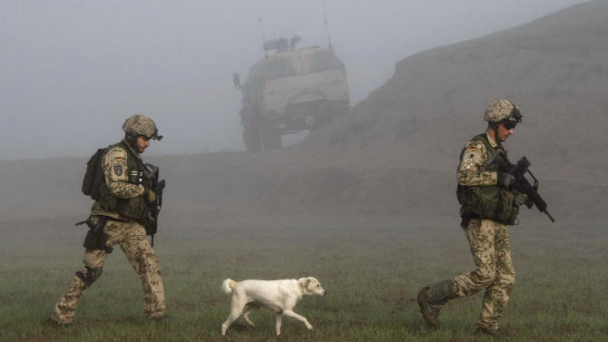 A dog follows German Bundeswehr army soldiers of the International Security Assistance Force (ISAF) during a mission in Chahar Dara