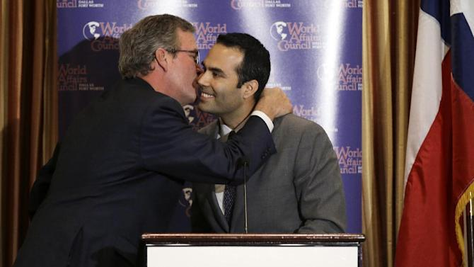 Former Governor Jeb Bush, left, gives his son George P. Bush, right a kiss on the cheek after George introduced him to attendees at the Dallas Council of World Affairs where Jeb was the featured speaker Wednesday, April 24, 2013, in Dallas. Jeb Bush and Hillary Rodham Clinton are hitting the speakers' circuit on the eve of the opening of George W. Bush's new presidential library, stoking speculation about their own political futures.(AP Photo/Tony Gutierrez)