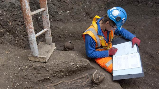 In this undated but recent photo supplied Friday March 15, 2015, by the London Crossrail Project, showing archaeologists working on the UK's largest infrastructure project, Crossrail, as they uncover an historical burial ground at Charterhouse Square, Farringdon in central London. Scientists were called in to investigate bones found during the digging of a new railway in central London, after uncovered 13 skeletons were found.  The skeletons will be tested to see if they died from the Black Death plague which killed between 30 and 60 percent of the European population in the 14th century, and scientist hope to map the DNA signature of the plague bacteria. (AP Photo / Crossrail Project)