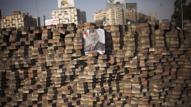 A picture of Egypt's ousted President Mohammed Morsi is displayed on a makeshift barricade in Nasr City, where protesters have installed a camp and hold daily rallies, in Cairo, Monday, July 29, 2013. Europe's top diplomat urged Egypt's government to reach out to the Muslim Brotherhood as she worked Monday to mediate an end to the country's increasingly bloody crisis, while the mainly Islamist protesters calling for the return of ousted leader Mohammed Morsi massed for more protests. (AP Photo/Manu Brabo)