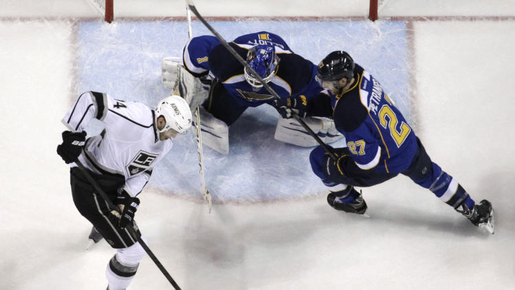 Los Angeles Kings' Justin Williams, left, tries to control the puck as St. Louis Blues goalie Brian Elliott and Blues' Alex Pietrangelo, right, defend during the first period in Game 5 of a first-round NHL hockey Stanley Cup playoff series, Wednesday, May 8, 2013, in St. Louis. (AP Photo/Jeff Roberson)