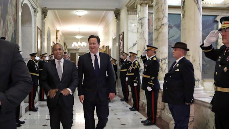 Massachusetts Gov. Deval Patrick, left, walks with British Prime Minister David Cameron through a corridor at the Statehouse in Boston, Monday, May 13, 2013. Cameron met with Patrick to offer his condolences and discuss lessons that can be learned from the Boston Marathon attacks. (AP Photo/Elise Amendola)