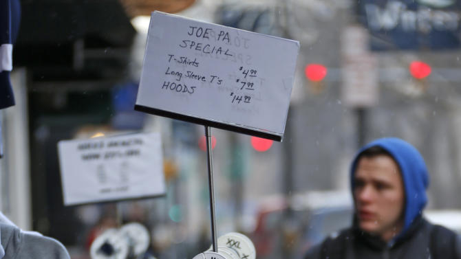 """""""Joe Knows Football"""" t-shirts and sweatshirts hang on a sales rack outside a shop in State College, Pa., Tuesday, Jan. 22, 2013. Supporters of Paterno are marking the 1-year anniversary of his death with a candlelight vigil Tuesday night.  (AP Photo/Gene J. Puskar)"""